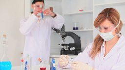 Scientists with masks conducting an experiment Stock Video Footage