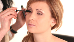 Blonde woman having her eyes made up by makeup art Stock Video Footage
