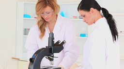 Scientist women looking through a microscope Stock Video Footage