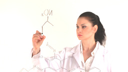 Scientist woman writing a formula while facing the Footage