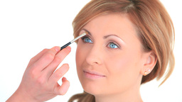 Young woman being made up by a makeup artist Stock Video Footage