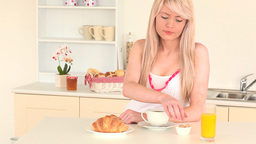 Blondhaired woman having her breakfast Stock Video Footage