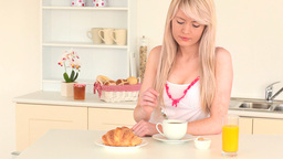 Blondhaired woman having her breakfast Footage