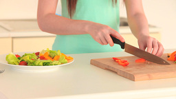 Woman slicing a red pepper while preparing a salad Footage