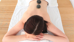 Brunette relaxing with hot stones on her back Footage