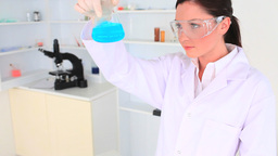 Young scientist wearing safety glasses and looking Footage