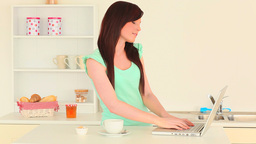 Young brunette chatting on her laptop while drinki Stock Video Footage