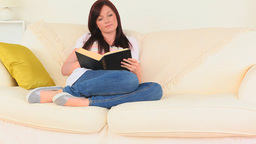 Darkhaired woman reading a book while sitting on t Footage