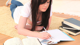 Young brunette studying while lying on the floor Footage