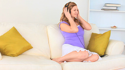 Delighted blondhaired woman listening to music Footage