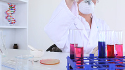 Female scientist carrying out an experiment Stock Video Footage