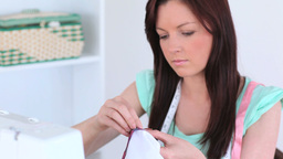 Attractive darkhaired woman sewing Footage