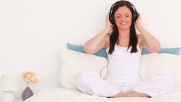 Young darkhaired woman listening to music Footage
