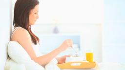 Attractive brunette eating her breakfast Stock Video Footage