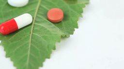 Close up of a green leaf with pills turning on its Footage