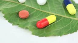 Close up of a green leaf with pills turning on its Stock Video Footage