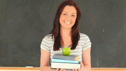 Attractive woman posing while holding some books Footage