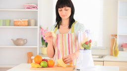 Darkhaired woman preparing a smoothie Footage