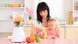 Mother and her baby daughter preparing a milkshake Footage