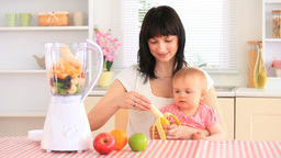 Mother and her baby daughter preparing a milkshake Stock Video Footage
