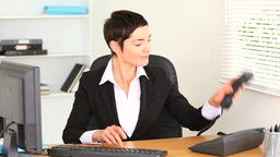 Brunette woman typing on a laptop and answering th Footage