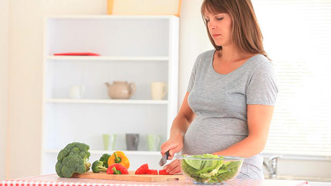 Happy pregnant woman cooking Footage