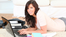 Brunette lying on a carpet using her laptop Stock Video Footage