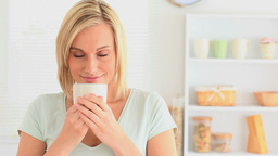 Blondhaired woman enjoying coffee Stock Video Footage