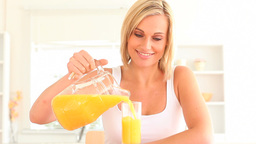 Blond woman pouring juice Stock Video Footage