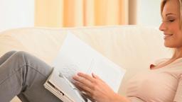 Gorgeous woman reading a magazine Live Action