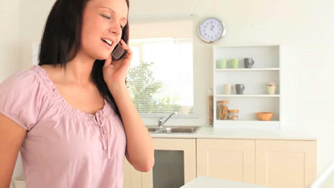 Woman answering to her phone while using her lapto Footage