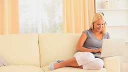 Cheerful blonde woman sitting on a sofa while surf Footage