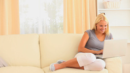Cheerful blonde woman sitting on a sofa while surf Stock Video Footage