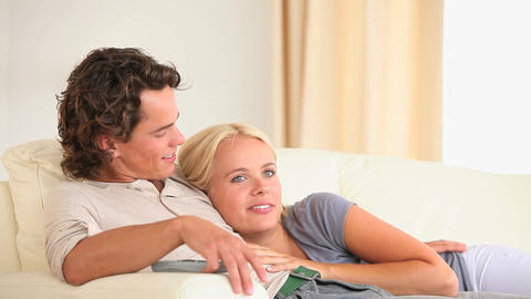 Happy couple on a sofa watching TV Stock Video Footage