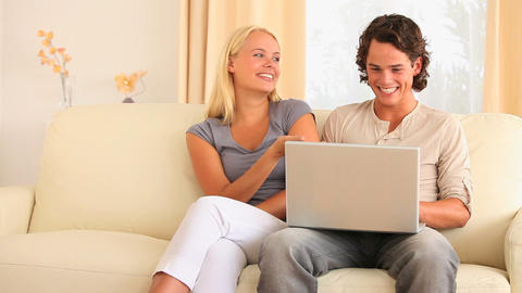 Couple sitting on a sofa searching the web Stock Video Footage