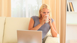 woman with a cup of coffee and a laptop sitting on Stock Video Footage