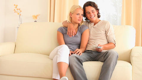 Cheerful couple sitting on a sofa watching TV Footage