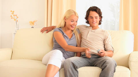 Cheerful couple sitting on a sofa watching TV figh Footage