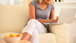 Woman lounging on a sofa searching the web Stock Video Footage