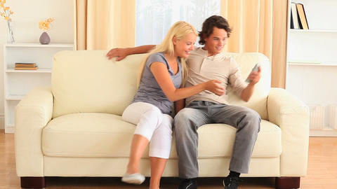 Happy young couple on the sofa fighting for remote Footage