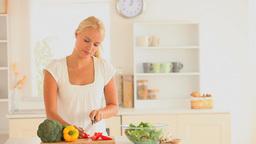 Lady slicing vegetables Footage