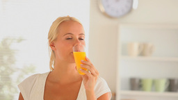 Woman drinking glass of orange juice Stock Video Footage