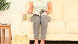 Shorthaired woman reading a magazine Stock Video Footage