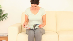 Shorthaired woman reading a magazine Live Action