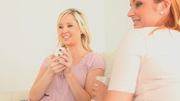 Young women chatting while drinking coffee Stock Video Footage
