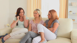 Women chatting while sitting on a sofa Footage