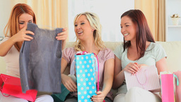 Cute woman showing new clothes to her friends Footage