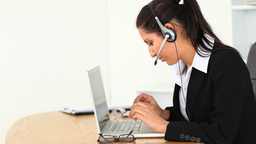 Businesswoman with a headset and a laptop Footage