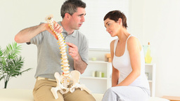 Chiropractor Explaining The Spine To A Woman stock footage