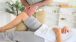 Masseur massaging a womans knee Footage